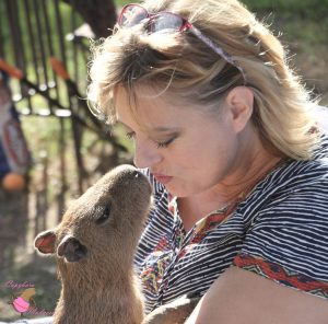 Woman holding baby capybara and kissing his nose